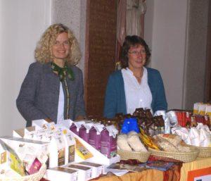 """Pia Stumpe und Gaby Franke an ihrem """"Fairstand"""" beim Verkauf der GEPA-Produkte in der Olchinger Kirche."""